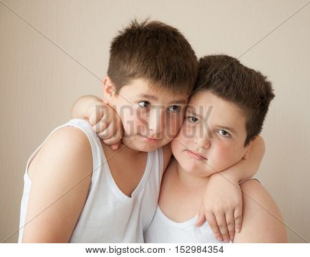 two cute boys in white t-shirts hugging