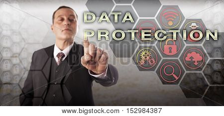 Mature business manager with perky expression is activating DATA PROTECTION onscreen. Information technology concept touching on information privacy criminal justice investigation and data security.