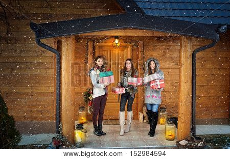Girls with gifts in front of weekend house on mountain
