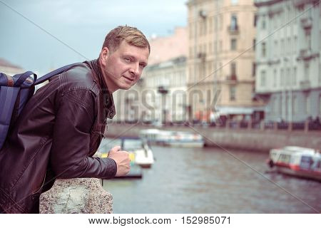 Man with backpack in the city on the waterfront