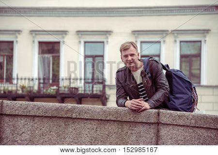 Man in town on the bridge with a backpack