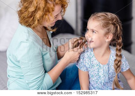 Happiness. Smiling grandmother plaiting braids to her little granddaughter while resting together