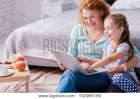 Funny weekend. Laughing little girl sitting on the floor with her grandmother while looking at the laptop