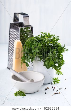 Cheese and herbs with grater and mortar bowl