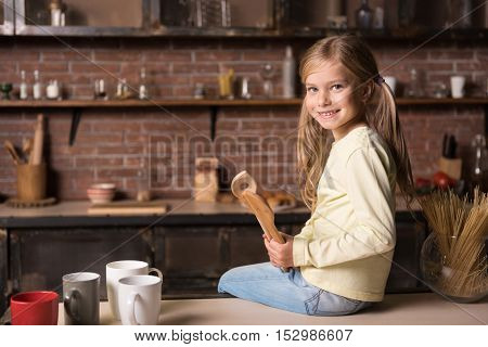 In a good mood. Cheerful delighted smiling little girl holding wooden spoons and sitting on the table while having fun in the kitchen