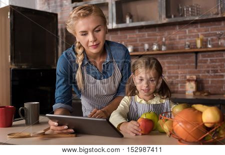 We cooking. Merry happy little girl holding apples and sitting at the table with her mother while expressing joy in the kitchen