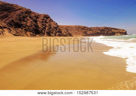 Beautiful beach La Pared with mixed golden and dark sand ocean waves and rocks on the Canary Island Fuerteventura Spain.