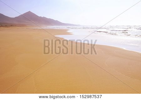 A famous huge beach La Cofete with golden sand and the maountains on the background in the morning in Fuerteventura.