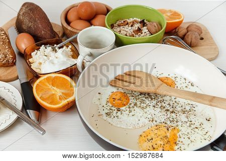 Fried eggs in the frying pan,breakfast ingredients.Orange,bread,kitchen accessories.Cooking morning food.White table