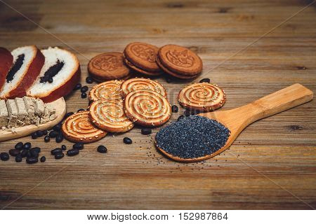 There are Pieces of  Roll with poppyseed,Cookies,Halavah,Chocolate Peas,Tasty Sweet Food on the Wooden Background