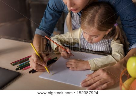 We enjoy drawing together. Involved cheerful happy girl drawing with her mother while sitting at the table and expressing fun at home