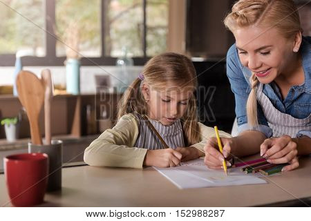 Positive atmosphere. Delighted amused cheerful mother drawing with her little daughter while sitting at the table and expressing joy in the kitchen