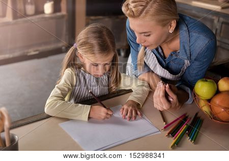 Enjoyable time together. Delighted amused cheerful mother drawing with her little daughter while sitting at the table and expressing joy in the kitchen