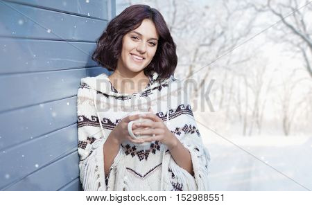 Beautiful natural young brunette woman with cup of coffee, wearing knitted poncho, standing at the house. Winter snowing weather and woods landscape in the background
