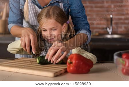 Let me help you. Amused delighted involved girl cutting a cucumber with her mother and sitting at the table in the kitchen while cooking and having fun
