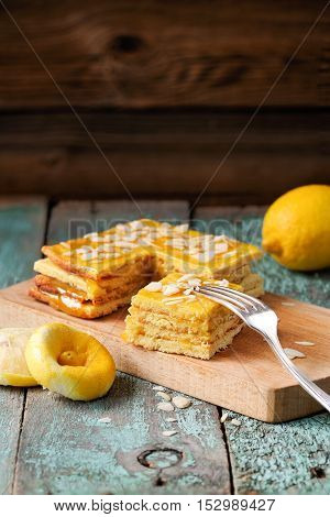 Homemade layered lemon cake with almonds on wooden board copyspace vertical