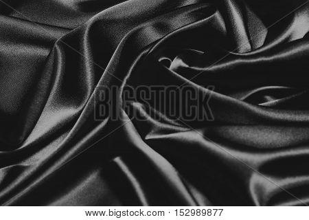 Closeup of rippled black silk fabric elegant background for design black and white background