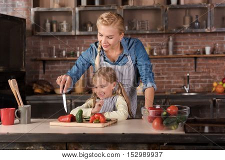 We playing games with paper. Delighted happy smiling woman cutting a pepper and standing near the table in the kitchen while cooking with her daughter