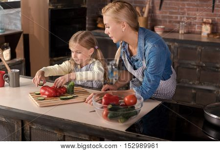 Cooking together. Pleasant peaceful nice woman looking at her daughter and standing near the table in the kitchen while cooking and having fun