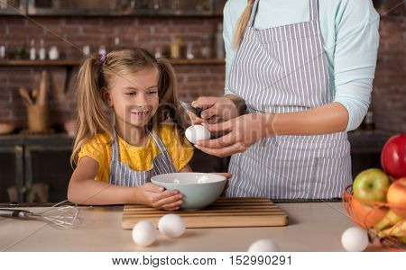 Joyful cooking with my mother. Pleasant smiling nice daughter breaking eggs with her mother and standing near the table in the kitchen while cooking and having fun