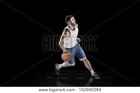 Young basketball player in action with ball isolated on black background