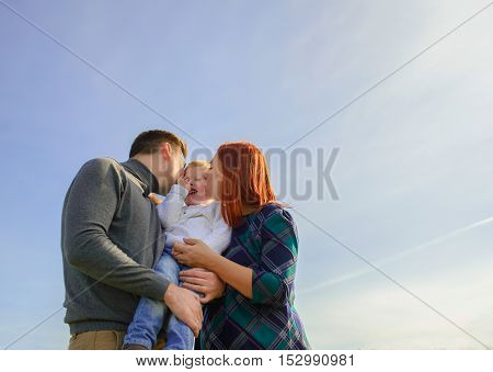 Family of three huging and kissing on the sky background.
