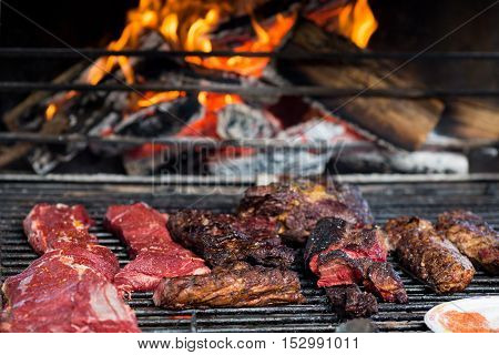 Close-up of pork grilled meat and raw slices on grill with fire background. Bbq, street food concept