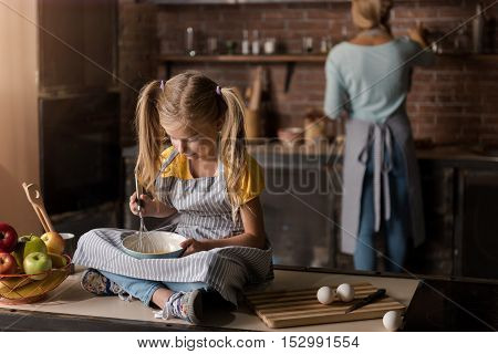 I want to help my mother. Pleasant cute concentrated girl holding the bowl and mixing eggs while sitting on the table in the kitchen and her mother cooking in the background