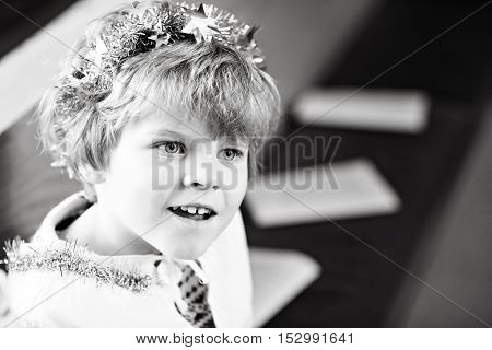 Beautiful little kid boy in church on Christmas eve, playing angel. Happy adorable blond child singing with lights and xmas tree on background.