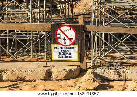 Construction scaffolding built under an overpass over the highway as the background. Sign - machinery mobile caution