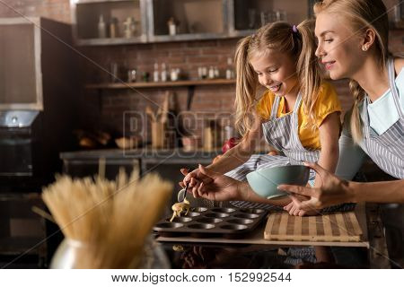 I enjoy bakery. Amused joyful little girl putting the pastry in baking rings with her mother while sitting on the table in the kitchen and cooking