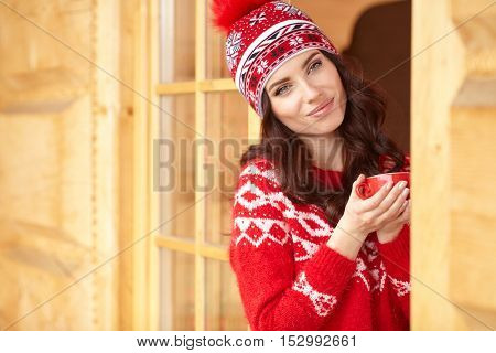woman wearing a sweater and a  hat holding a cup of warm drink outdoors.