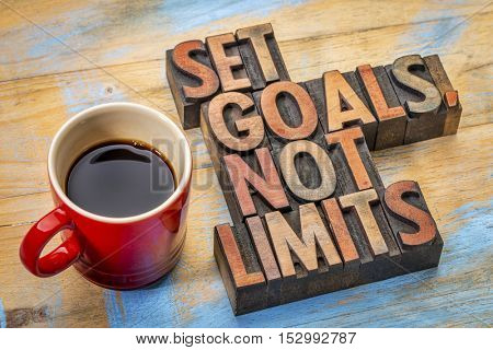 Set goals, not limits - motivational advice in vintage letterpress wood type with a cup of coffee