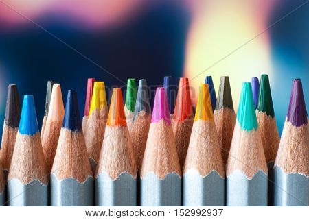 Sharpened colored pencils. A stack of colored pencils. Ready to paint. Colored pencils on a colorful background.