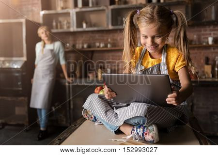 I searching for interesting recipe. Delighted amused little girl looking at the tablet and sitting on the table in the kitchen while expressing joy and her mother standing in the background