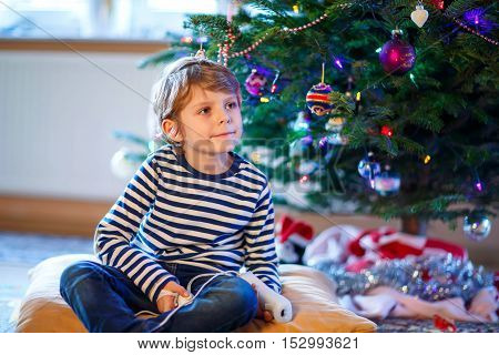 Cute little blond kid boy playing with a video game console on Christmas with decorated tree on background. Child having fun at home.