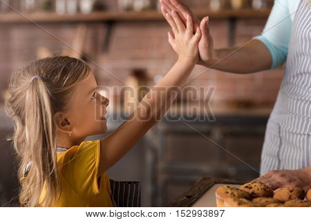 We did it. Pleasant joyful little girl giving five to her mother while standing in the kitchen and expressing joy