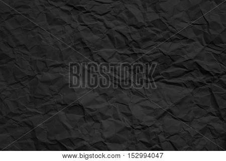 Texture of crumpled dark paper. Closeup photo.