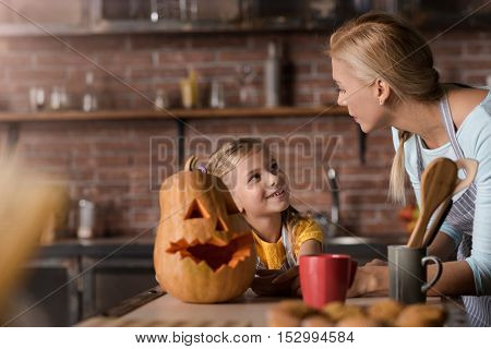 Halloween is soon. Cheerful delighted little girl preparing a pumpkin for Halloween with her mother while standing in the kitchen near the table and expressing joy