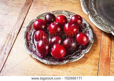 Fresh juicy plums in a vintage plate on wooden table