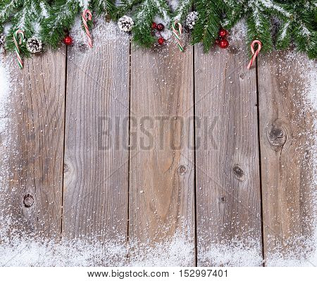 Wooden background for Christmas concept with fir branches covered in snow. Overhead view with copy space.