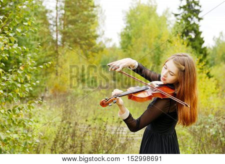 Beauty girl playin violin in the forest
