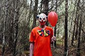 a scary evil clown wearing a dirty costume, holding a red balloon in his hand, in the woods poster