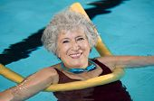 Senior woman doing aqua fitness with swim noodles. Mature woman doing water aerobics with a yellow n poster
