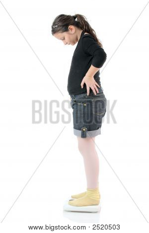 Little Girl Standing On A Weight Scale