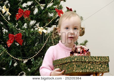 Little Girl Near The Christmas Tree Holding A Present
