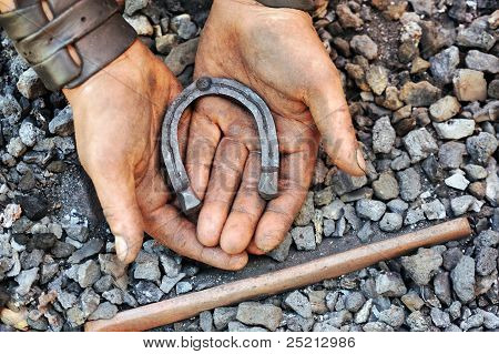Detail of dirty hands holding horseshoe