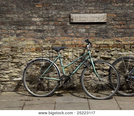 Bicycle leaning against brick wall