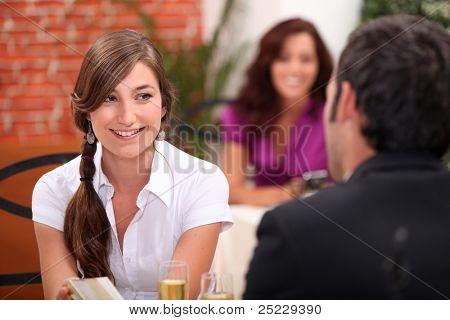 uma jovem mulher e um homem no restaurante, o vinho espumante flautas na mesa