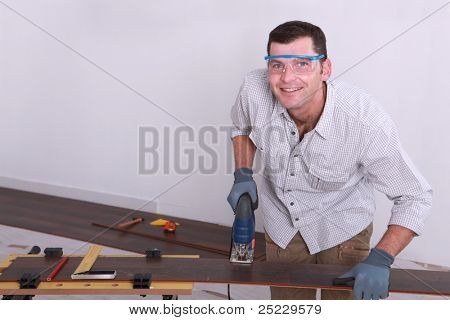 Man cutting tongue and groove floorboards with a jigsaw